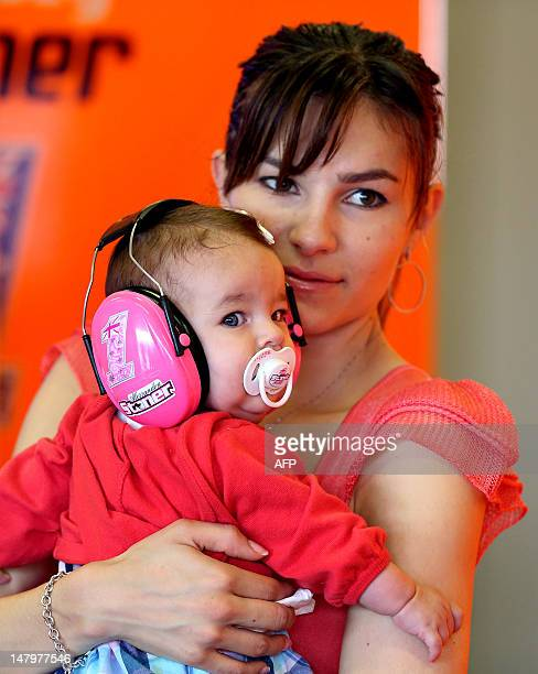 Adriana Stoner, wife of Australia's driver Casey Stoner of the Repsol Honda team, waits with their daughter Alessandra during the third training...