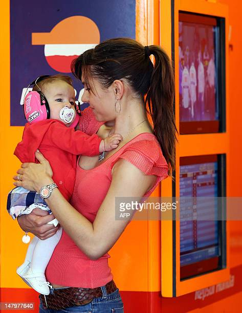 Adriana Stoner wife of Australia's driver Casey Stoner of the Repsol Honda team waits with their daughter Alessandra during the third training...