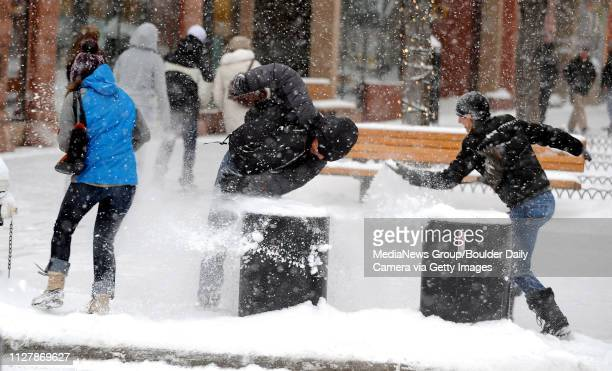 Adrianna Baraco left and Nina Duerst right surround a friend during a snow ball fight along the Pearl Street Mall on Thursday