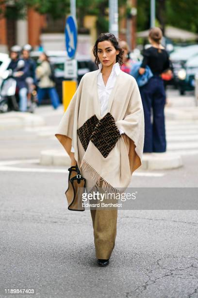 Adrianne Ho wears a white shirt, a cream-color fringed Fendi poncho, a camel bag, light brown wide-legs pants, black pointy shoes, outside the Fendi...