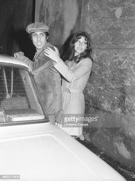 Adriano Celentano at the exit of a night club with a friend in Rome in 1972 He is a famous Italian singer composer producer comedian actor film...
