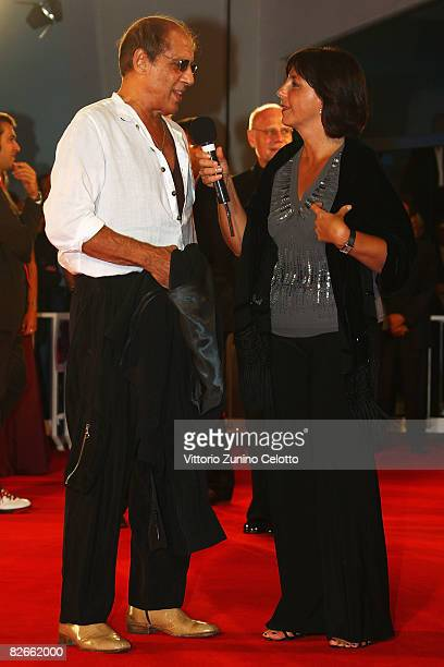 Adriano Celentano is beeing interviewed on the red carpet while attending the Yuppi Du premiere at the Sala Grande during the 65th Venice Film...