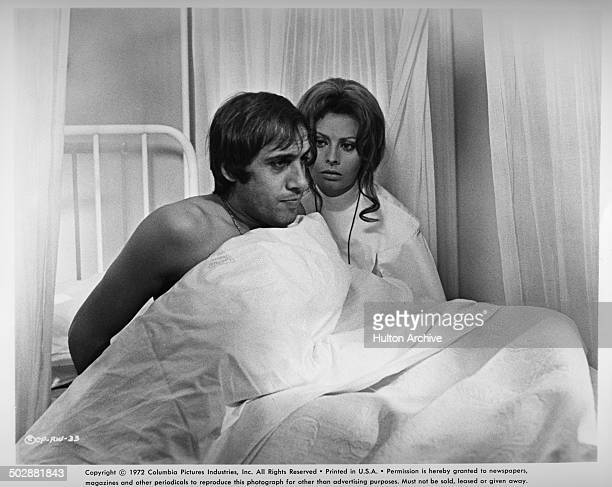 Adriano Celentano sits up in bed with Sophia Loren in a scene from the movie 'White Sister' circa 1972