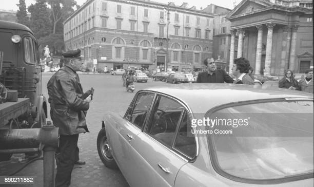 Adriano Celentano with the traffic policemen while they take away the car parked in a no parking area, Rome 1976. Adriano Celentano is a famous...