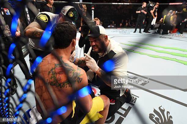 Adriano Martins of Brazil receives advice from his corner inbetween rounds while facing Leonardo Santos of Brazil in their lightweight bout during...