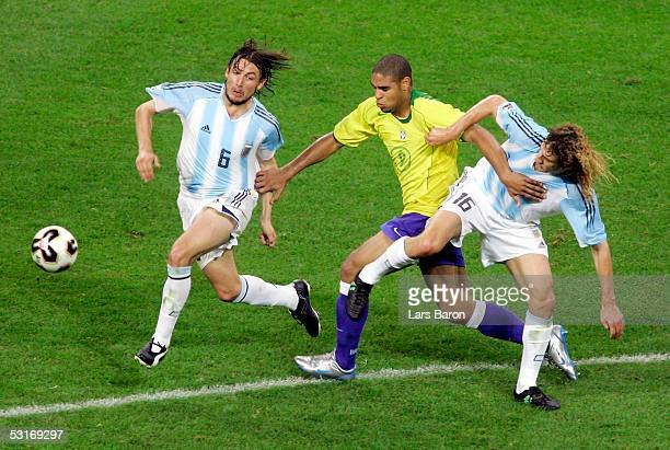 Adriano of Brazil goes between Gabriel Heinze and Fabricio Coloccini of Argentina during the FIFA 2005 Confederations Cup Final between Brazil and...