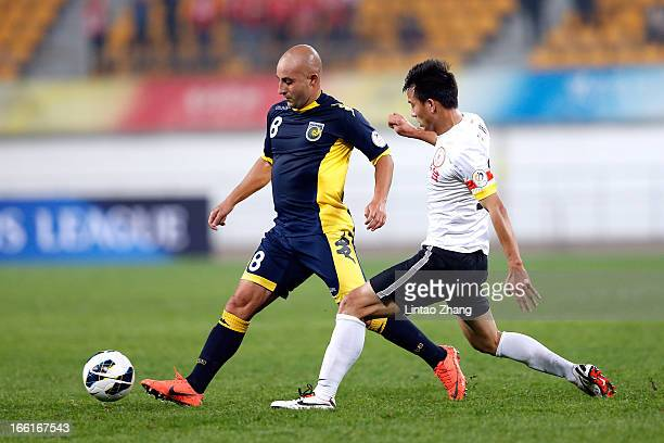 Adriano Pellegrino of the Mariners challenges Sun Jihai of Guizhou Renhe during the AFC Champions League match between Guizhou Renhe and Central...