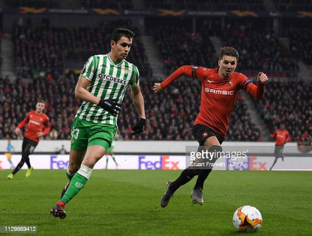 Adrien Hunou of Rennes is challenged by Aïssa Mandi of Betis during the UEFA Europa League Round of 32 First Leg match between Stade Rennais and Real...