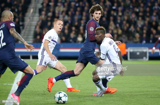 Adrien Rabiot of PSG between Adrien Trebel and Henry Onyekuru of Anderlecht during the UEFA Champions League group B match between Paris SaintGermain...