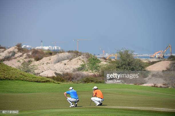 Adrien Saddier of France and Garrick Porteous of England line up their putts during day four of the NBO Golf Classic Grand Final at Al Mouj Golf on...