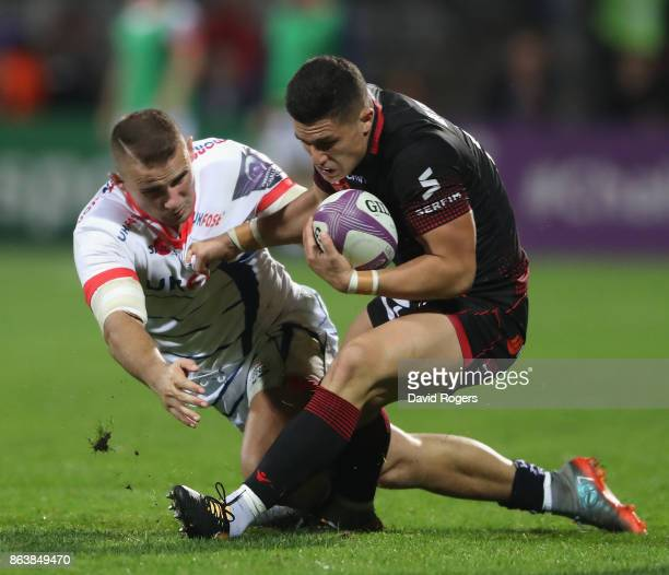 Adrien Seguret of Lyon is tackled by Mark Jennings during the European Rugby Challenge Cup match between Lyon and Sale Sharks at Matmut Stade de...