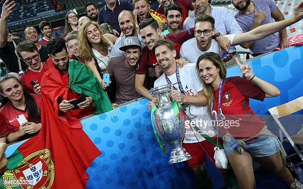 Adrien Silva of Portugal and his wife Margarida Neuparth pose with the trophy following the UEFA Euro 2016 final match between Portugal and France at...
