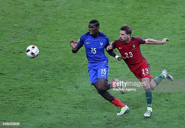 Adrien Silva of Portugal in action against Paul Pogba of France during the Euro 2016 final match between Portugal and France at Stade de France in...