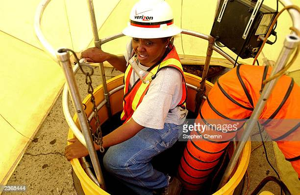Adriene Edwards a Verizon technician for seven years climbs out of a tented manhole while working on the Upper West Side August 4 2003 in New York...