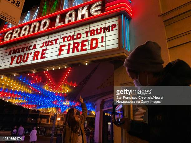"""Adrienne Lam has her photo taken by Andrew Lee, both of Oakland, underneath the marquee at Grand Lake Theatre that reads, """"America just told Trump,..."""