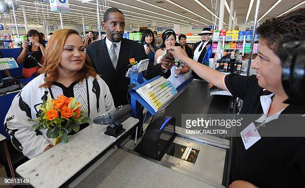 Adrienne Rounds and Brad Pye pay for their 99 cent wedding ceremony at a checkout at the 99 cent store in Los Angeles on September 9 2009 The budget...