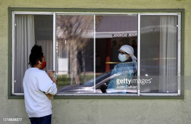 Adrina Rodriguez talks with a nurse through a window as she visits her father who is a patient at the Gateway Care and Rehabilitation Center that has...