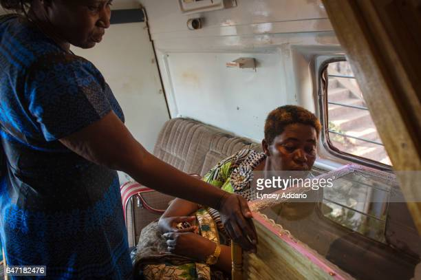 Adrine Ashaba and Peace Magoba look at the dead body of their sister Jolly Komurembe hours after she died of advanced breast cancer and before being...