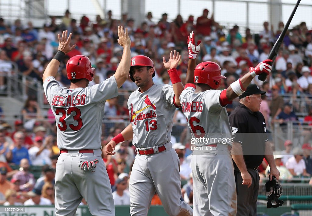 Adron Chambers #56, Daniel Descalso #33 and Matt Carpenter #13 of the St. Louis Cardinals celebrate after scoring on a double to center field from Tony Cruz #48 during the third inning of the game against the Boston Red Sox at JetBlue Park on February 26, 2013 in Fort Myers, Florida.