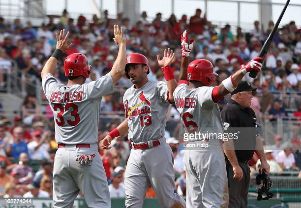 Adron Chambers Daniel Descalso and Matt Carpenter of the St Louis Cardinals celebrate after scoring on a double to center field from Tony Cruz during...