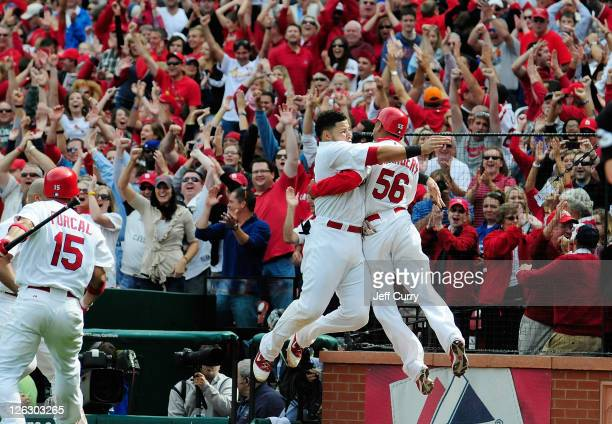 Adron Chambers of the St Louis Cardinals celebrates with Yadier Molina after scoring on a wild pitch by Carlos Marmol of the Chicago Cubs in the...