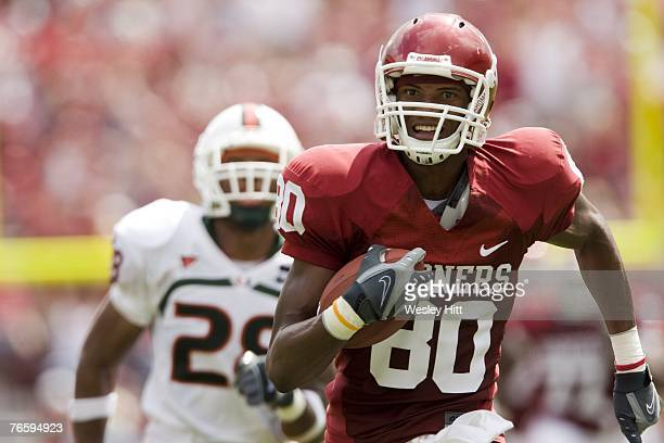 Adron Tennell of the Oklahoma Sooners runs a pass for a touchdown against the Miami Hurricanes at Gaylord FamilyOklahoma Memorial Stadium September 8...