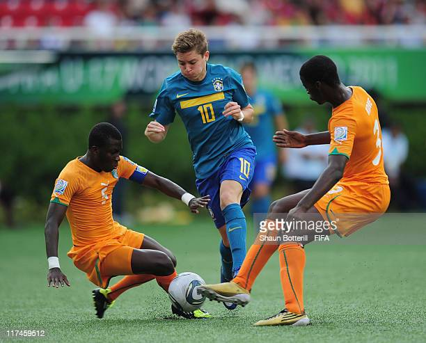 Adryan of Brazil is tackled by Mory Kone and Jean Thome of Ivory Coast during the FIFA U-17 World Cup Group F match between Ivory Coast and Brazil at...
