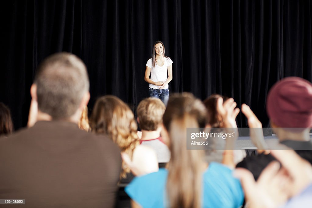 Adudience clapping for a teenage girl on stage : Stock Photo