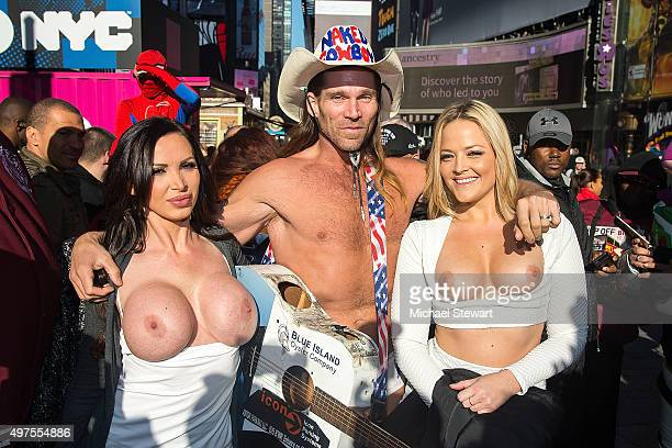 Adult actresses Nikki Benz and Alexis Texas pose topless with the Naked Cowboy in celebration of gender liberation in Times Square on November 17...