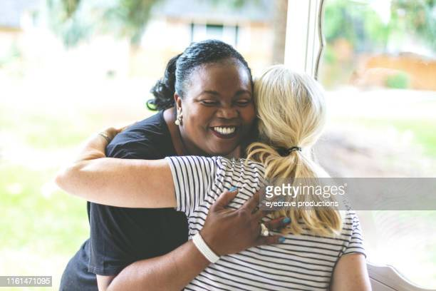 adult african american female and caucasian at front door of residence greeting each other with an embrace - embracing stock pictures, royalty-free photos & images