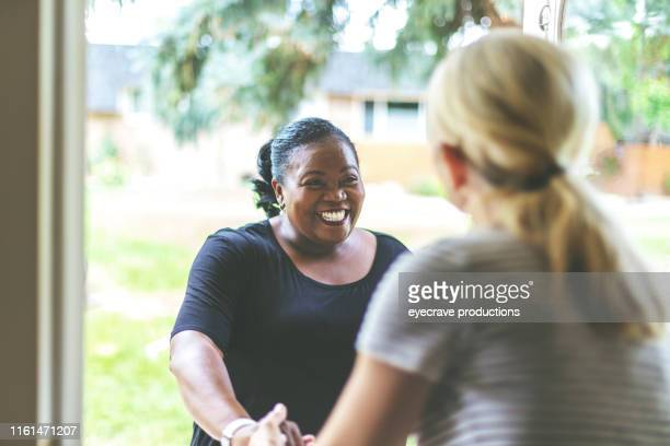 Adult African American Female and caucasian at front door of residence greeting each other with a handshake