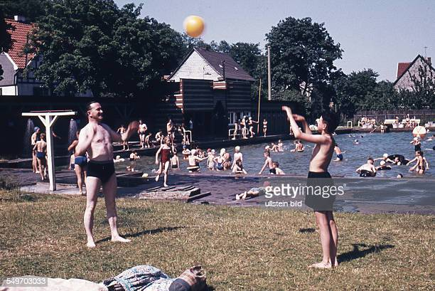 Adult and boy play with a ball in an open air pool