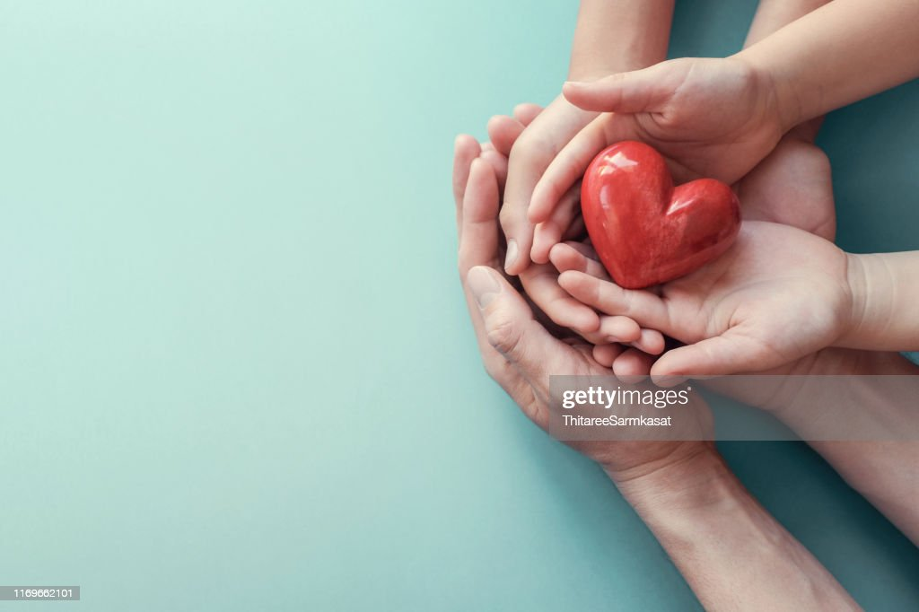 adult and child hands holding red heart on aqua background, heart health, donation, CSR concept, world heart day, world health day, family day : Stock Photo