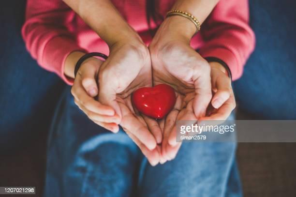 erwachsene und kinderhände mit rotem herzen - spende für wohltätige zwecke stock-fotos und bilder
