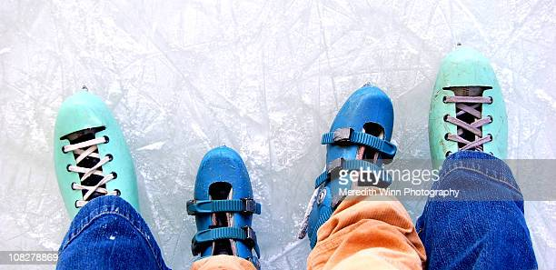 adult and child ice skates standing on ice - ice skate stock pictures, royalty-free photos & images