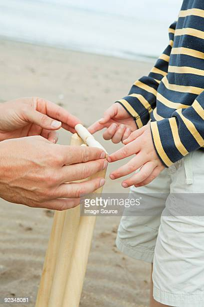 adult and child setting up crickets stumps - beach cricket stock pictures, royalty-free photos & images