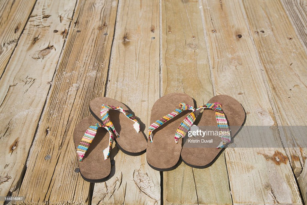 5e0a70716b27f4 Adult and child sized flip flops on boardwalk   Stock Photo