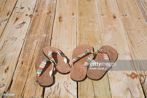 Adult and child sized flip flops on boardwalk