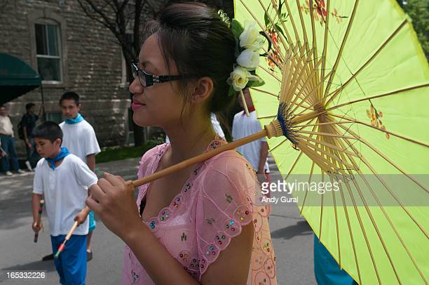 Adult asian woman in strong sunlight, lighted from behind as a green sun parasol protects her from the direct sunlight. Children in blue and white...