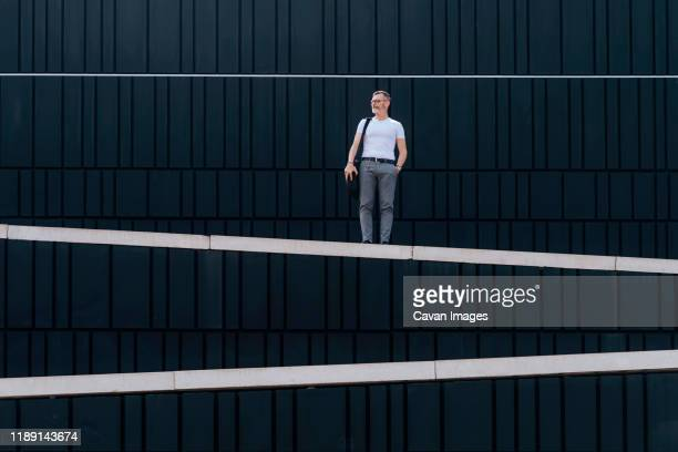 adult bearded man with shoulder bag standing against wall in the city - symmetry stock pictures, royalty-free photos & images