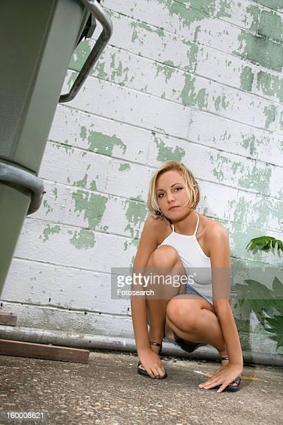 Adult blonde woman kneeling beside building in alley looking at viewer.