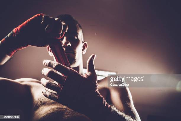 adult boxer tying protective cloth aroung his wrists - boxing stock pictures, royalty-free photos & images