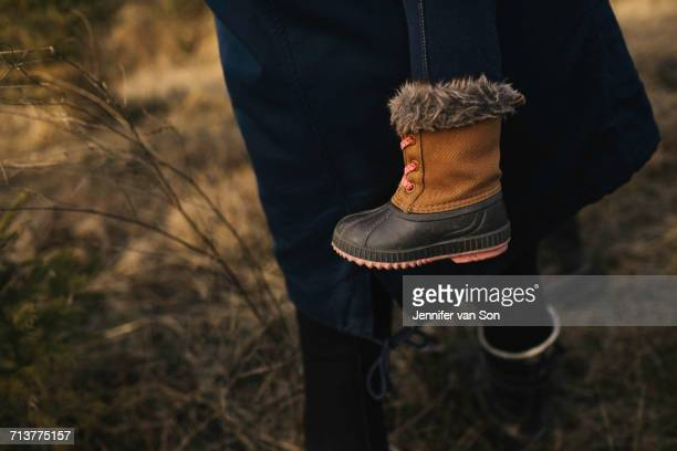 adult carrying child, close up of childs boot - bottines photos et images de collection