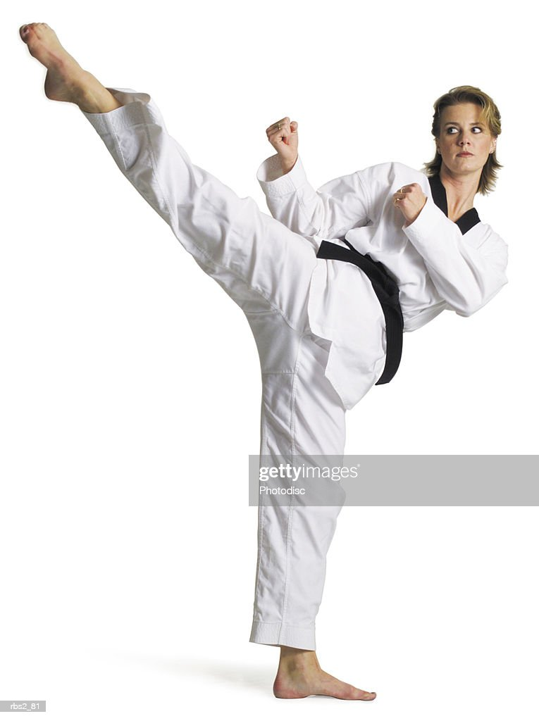 adult caucasian female martial arts expert in white with blackbelt performs roundhouse kick to right : Foto de stock