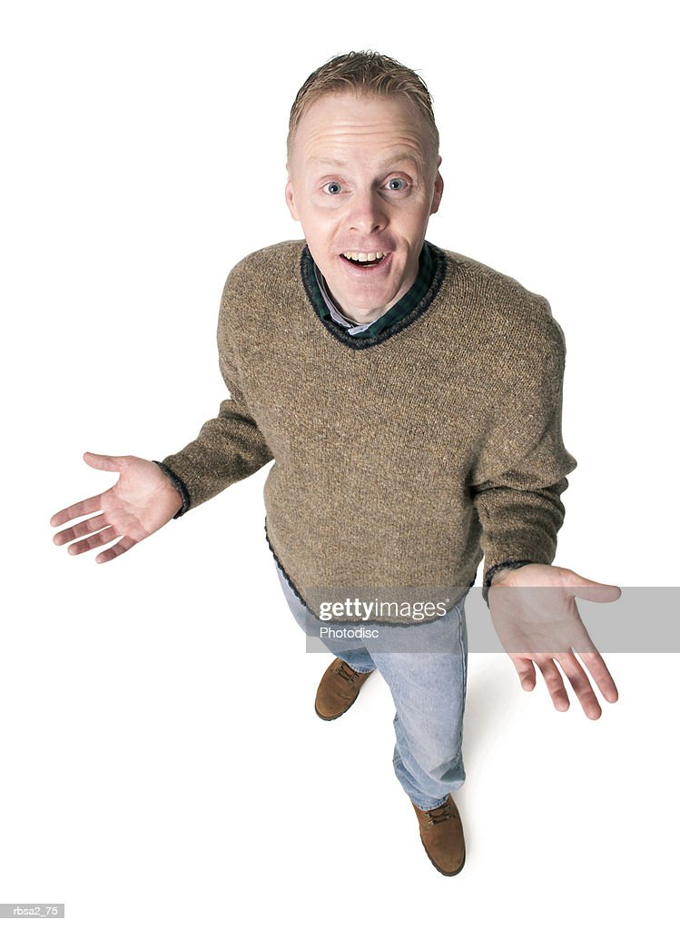 adult caucasian man dressed in jeans and green sweater gestures with his hands shrugs his shoulders : Stock Photo