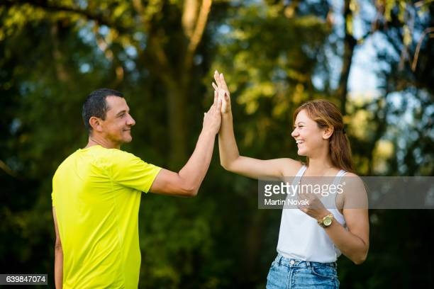 adult cheerful daughter doing high-five with her father - taper dans les mains photos et images de collection