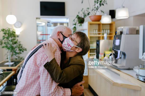 adult child greeting father with hug - tourist stock pictures, royalty-free photos & images