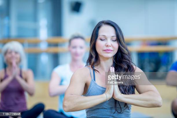 adult co-ed yoga class stock photo - 40 49 years stock pictures, royalty-free photos & images
