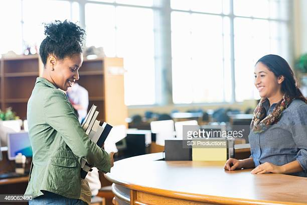 adult college student is holding stack of books in library - book store stock photos and pictures