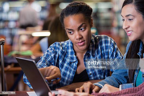 Adult college student studying together in crowded library